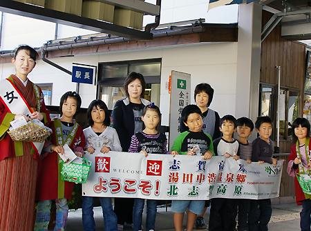 旅行客の到着を待つ女将と地元の小学生